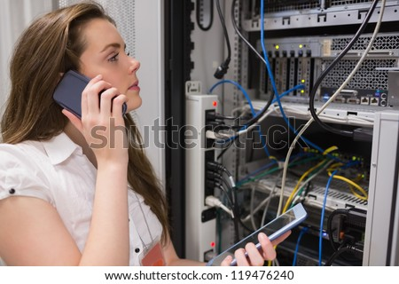 Woman working on servers with tablet pc on the phone in data center - stock photo