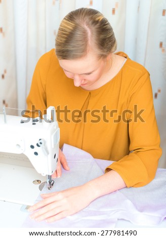 Woman working on sewing machine in the factory. - stock photo