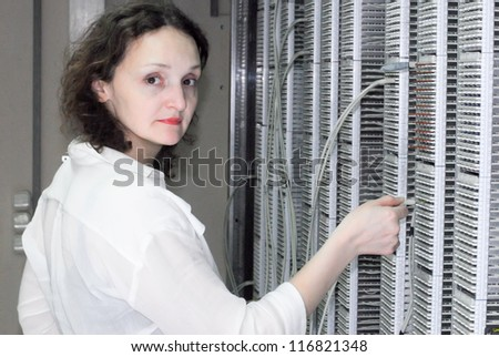 Woman working on technical site of mobile switching center for connection cellular phones