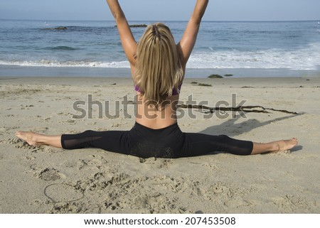 Woman working out at the beach/Beach Fitness/Attractive woman is doing stretches and yoga on the beach - stock photo