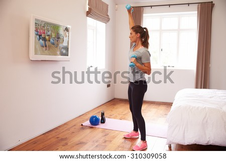 Woman Working Out To Fitness DVD On TV In Bedroom - stock photo