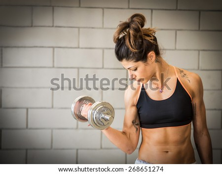 Woman working out with dumbbell - Sportive girl training her bicep  - stock photo