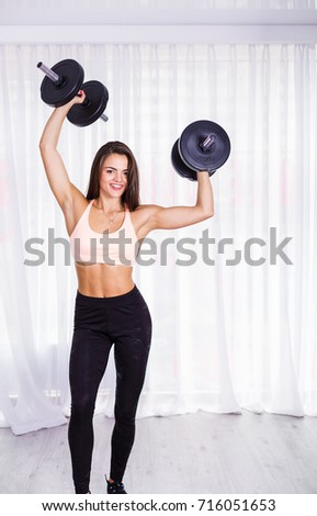 Woman working out with dumbbells in the fitness studio
