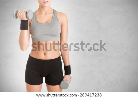 Woman working out with dumbbells, isolated in grey - stock photo