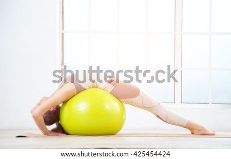 Woman working out with exercise ball in gym. Pilates woman doing exercises in the gym workout room with fitness ball. Fitness woman doing exercises for muscle press with abs swiss ball. - stock photo