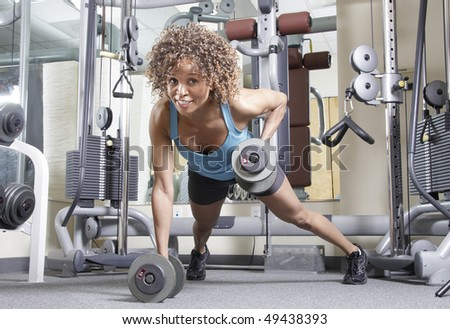 Woman working out with weights in a gym - stock photo