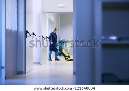 Woman working, professional maid cleaning and washing floor with machinery in industrial building