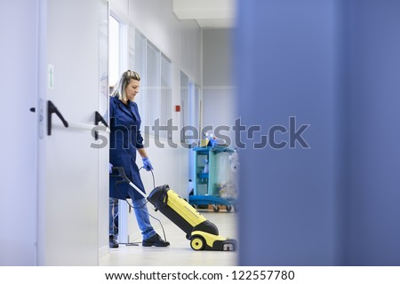 Woman working, professional maid cleaning and washing floor with machinery in industrial building. Full length, copy space - stock photo