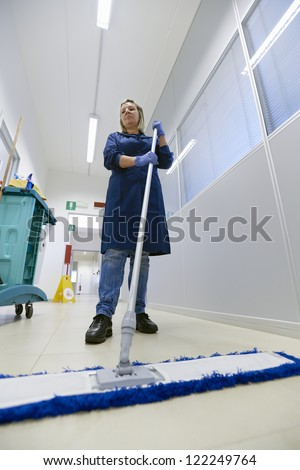 Woman working, professional maid cleaning floor with broom in industrial building. Full length, low angle view