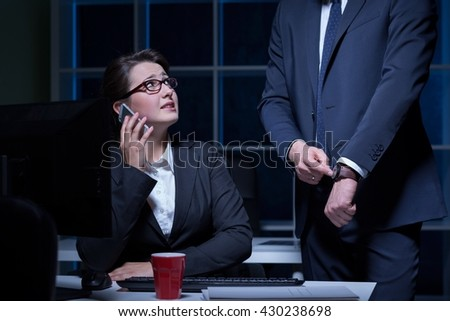 Woman working under pressure at night, sitting beside desk, man pointing his wristwatch - stock photo