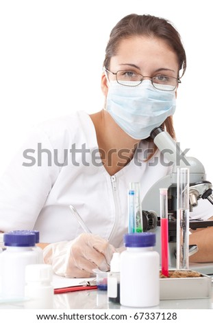 Woman working with a microscope and writing her experiment