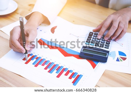 woman working with calculator with financial data analyzing hand calculate writing and counting in office. business workplace strategy Concept.
