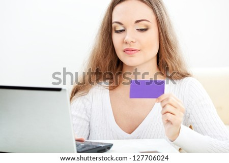 woman working with laptop and holding blank bank card