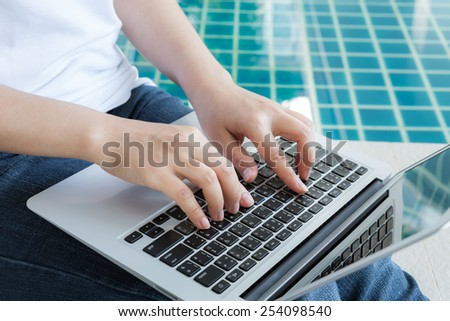 Woman working with laptop computer sitting at swimming pool