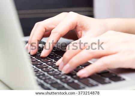woman working with laptop, finger typing on laptop keyboard