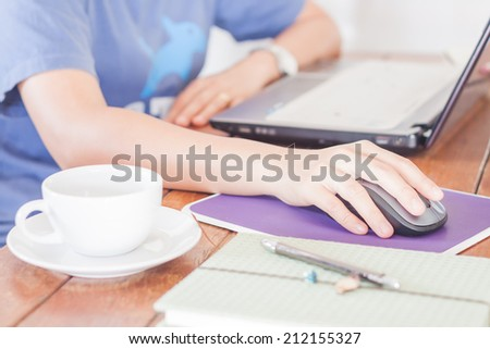 Woman working with laptop in coffee shop
