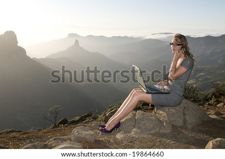 woman working with laptop in the mountain and talking by phone - stock photo
