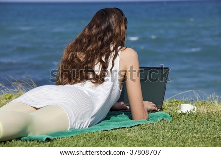 woman working with laptop on the beach in the sun