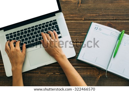 Woman working with laptop placed on the wooden desk - stock photo