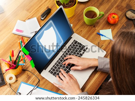 Woman working with laptop placed on wooden desk with digital scheme of security. Shot from aerial view - stock photo