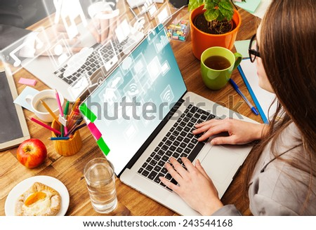 Woman working with laptop placed on wooden desk with digital scheme. Shot from aerial view - stock photo