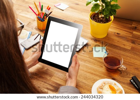 Woman working with tablet in office with wooden table - stock photo