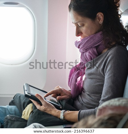 Woman working with tablet inside airplane.