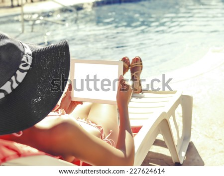 Woman working with tablet sitting at swimming pool. Vintage image. - stock photo