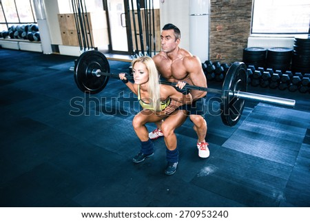 Woman workout with barbell with coach at gym - stock photo