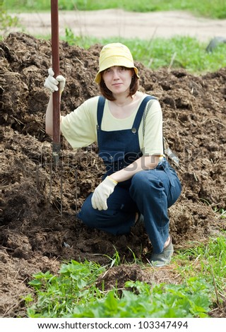 Woman works with animal manure at field