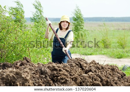 Woman works with animal manure at field - stock photo