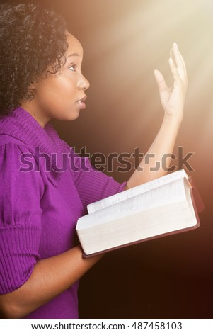 Woman worshiping God holding bible