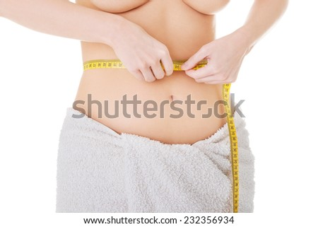 Woman wrapped in towel measuring her waistline - stock photo