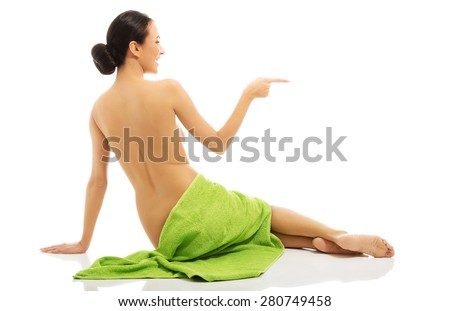 Woman wrapped in towel pointing to the left. - stock photo