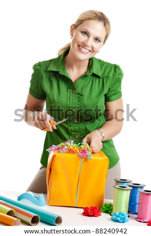 Woman wrapping a gift isolated on a white background - stock photo