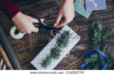 Woman Wrapping and Decorating Christmas Presents