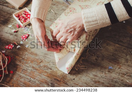 Woman wrapping modern Christmas gifts presents at home - stock photo