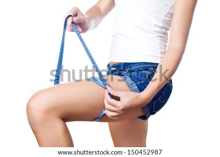 Woman wrapping tape measure around thigh