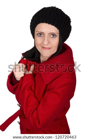 woman wrapping up warm in coat and hat against white background