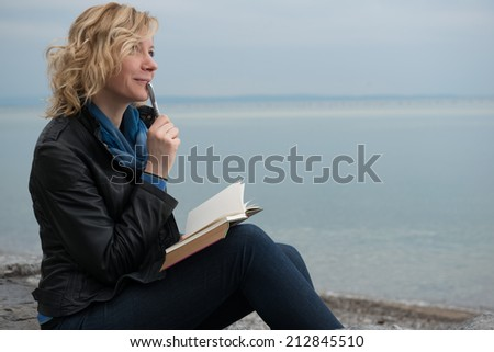 Woman writing her thoughts or poetry by the sea - stock photo