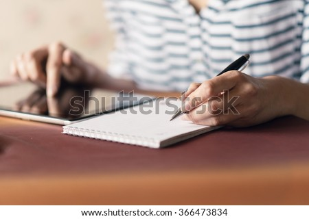 Woman Writing in a Notebook. Selective focus small depth of field and natural light.