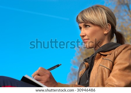 Woman writing in a park, sky on the background.