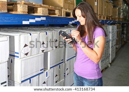 Woman Writing in Barcode Scanner for Warehouse Invertory Management - stock photo
