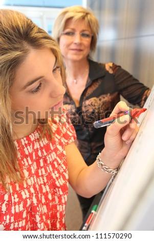Woman writing on a flip chart - stock photo