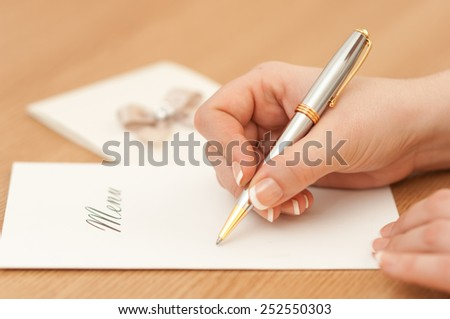 Woman writing on a wedding menu.