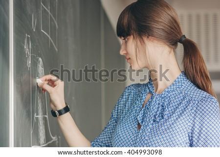 Woman writing on blackboard - stock photo