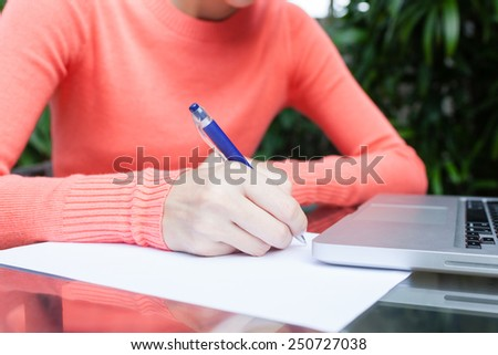 Woman writing on paper - stock photo