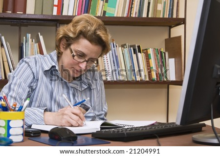 Woman writing something at her home business desk.