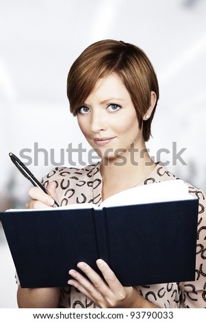 woman writing something in a note pad - stock photo