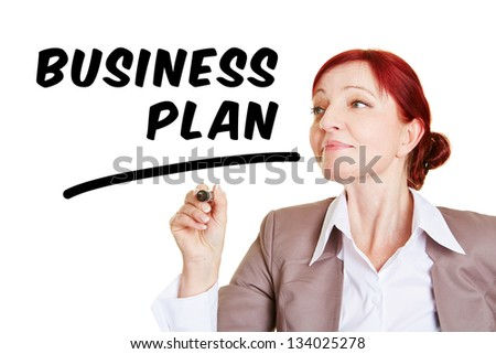 Woman writing the word business plan with pen in the air - stock photo